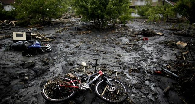 A bicycle lies on a street that was hit by floods in Topcic Polje